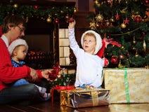 Padre y niños con los presentes en la Navidad Imágenes de archivo libres de regalías