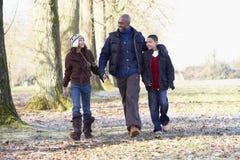 Padre y niños en caminata del otoño Foto de archivo libre de regalías