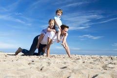 Padre y niños en la playa Fotografía de archivo libre de regalías