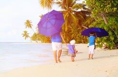 Padre y niños en la playa con los paraguas a ocultar Foto de archivo
