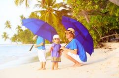 Padre y niños en la playa con los paraguas a ocultar Foto de archivo libre de regalías