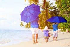 Padre y niños en la playa con los paraguas a ocultar Imágenes de archivo libres de regalías