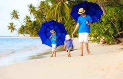 Padre y niños en la playa con los paraguas a ocultar Fotografía de archivo libre de regalías
