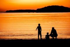 Padre y niños en la puesta del sol Fotos de archivo libres de regalías