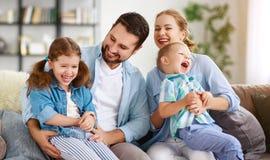 Padre y niños felices de la madre de la familia en casa en el sofá imagenes de archivo