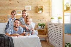 Padre y niños felices hija e hijo de la madre de la familia en cama foto de archivo