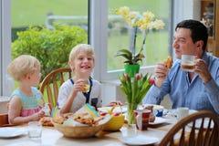 Padre y niños que comen en la cocina Fotos de archivo libres de regalías