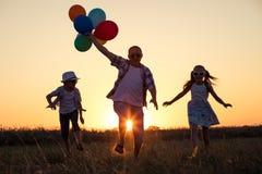 Padre y niños que corren en el camino en el tiempo de la puesta del sol Imagen de archivo libre de regalías