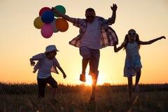 Padre y niños que corren en el camino en el tiempo de la puesta del sol Fotos de archivo libres de regalías