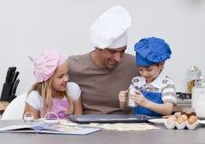 Padre y niños que cuecen al horno en la cocina fotos de archivo