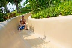 Padre y niños que deslizan abajo la diapositiva de agua Foto de archivo libre de regalías