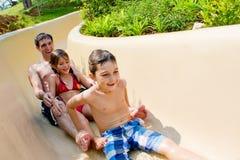 Padre y niños que deslizan abajo la diapositiva de agua Imágenes de archivo libres de regalías