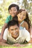 Padre y niños que disfrutan de día en parque fotos de archivo libres de regalías