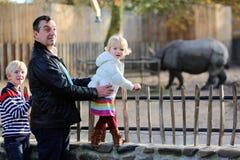 Padre y niños que disfrutan de día soleado en el parque zoológico Imagen de archivo libre de regalías