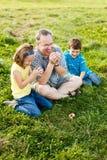 Padre y niños que intentan silbar Foto de archivo