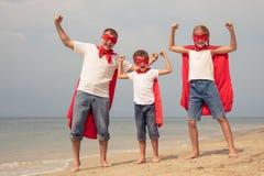 Padre y niños que juegan al super héroe en la playa en el ti del día Fotos de archivo