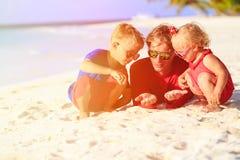 Padre y niños que juegan con la arena en la playa Imágenes de archivo libres de regalías