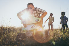Padre y niños que juegan en el camino en el tiempo del día Foto de archivo