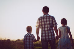 Padre y niños que juegan en el parque en el tiempo de la puesta del sol Imagen de archivo