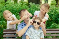 Padre y niños que juegan en el parque en el tiempo del día Foto de archivo