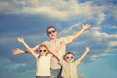 Padre y niños que juegan en el parque en el tiempo del día Imagen de archivo libre de regalías