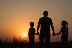 Padre y niños que juegan en el parque en el tiempo de la puesta del sol Fotografía de archivo