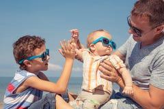 Padre y niños que juegan en la playa en el tiempo del día Imagen de archivo libre de regalías
