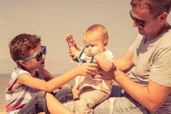 Padre y niños que juegan en la playa en el tiempo del día Fotografía de archivo