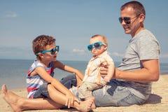 Padre y niños que juegan en la playa en el tiempo del día Imagen de archivo