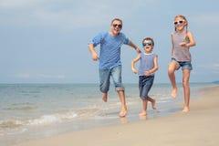 Padre y niños que juegan en la playa en el tiempo del día Imágenes de archivo libres de regalías