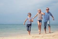 Padre y niños que juegan en la playa en el tiempo del día Fotos de archivo