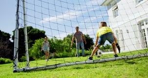 Padre y niños que juegan a fútbol almacen de metraje de vídeo