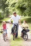 Padre y niños que montan las bicis en campo fotografía de archivo libre de regalías