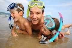 Padre y niños que ponen en la playa Fotografía de archivo