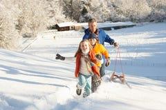 Padre y niños que tiran del trineo encima de la colina Nevado Imágenes de archivo libres de regalías