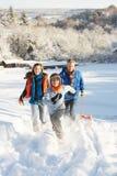 Padre y niños que tiran del trineo encima de la colina Nevado Foto de archivo libre de regalías