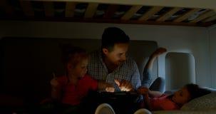 Padre y niños que usan la tableta digital en el dormitorio en casa 4k almacen de video