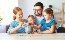 Padre y ni?os de la madre de la familia de la planificaci?n financiera con la hucha en casa imagen de archivo