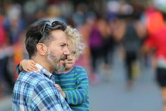 Padre y niño que miran el evento Imágenes de archivo libres de regalías