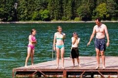 Padre y niños en el lago Fotos de archivo libres de regalías