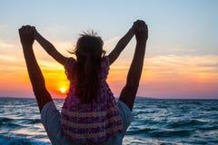 Padre y pequeña hija en la playa en la puesta del sol Imagenes de archivo
