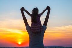 Padre y pequeña hija en la playa en la puesta del sol Foto de archivo