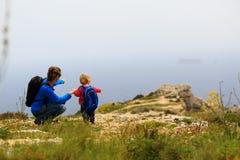 Padre y pequeña hija que caminan en montañas Foto de archivo
