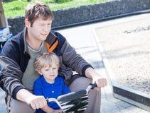 Padre y pequeño hijo que juegan junto al aire libre en el coche del juguete Imagen de archivo libre de regalías