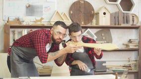 Padre y pequeño hijo que llevan los vidrios protectores que prueban la madera hecha a mano metrajes