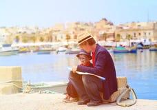 Padre y pequeño hijo que miran el mapa, familia Fotografía de archivo libre de regalías