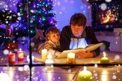 Padre y pequeño libro de lectura lindo del niño pequeño por la chimenea, las velas y la chimenea Foto de archivo libre de regalías