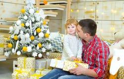 Padre y poca hija que juegan cerca del árbol de navidad fotografía de archivo libre de regalías