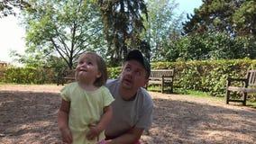 Padre y poca mirada de la hija al cielo en parque del verano en día almacen de metraje de vídeo