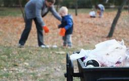 Padre y poco barrido del hijo en el parque Fondo - basura y cubo de la basura El concepto de ecología y de proteger el planeta imagenes de archivo